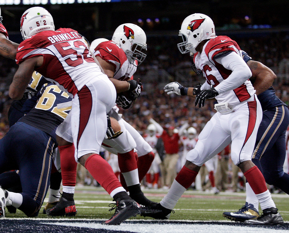 . Arizona Cardinals defensive tackle Dan Williams, center, returns an interception for a touchdown as teammates Jasper Brinkley (52) and Karlos Dansby, right, watch during the third quarter of an NFL football game against the St. Louis Rams, Sunday, Sept. 8, 2013, in St. Louis. (AP Photo/Tom Gannam)