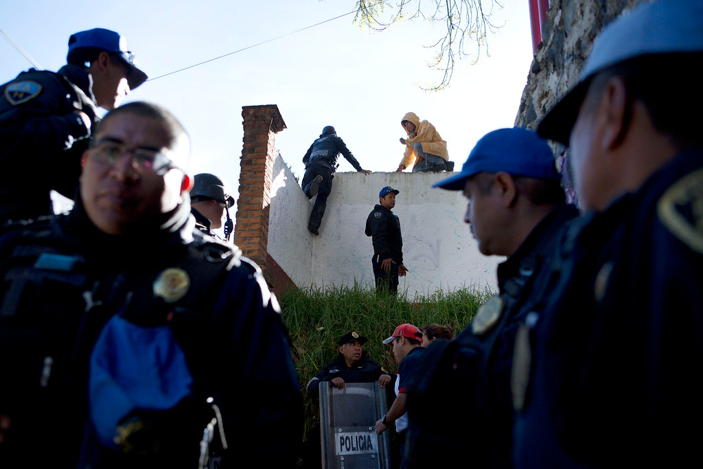 . Police climb over a wall, as they work to cordon off an area where rescue workers comb through the rubble of a children\'s hospital after a gas truck exploded, in Cuajimalpa on the outskirts of Mexico City, Thursday, Jan. 29, 2015. (AP Photo/Rebecca Blackwell)