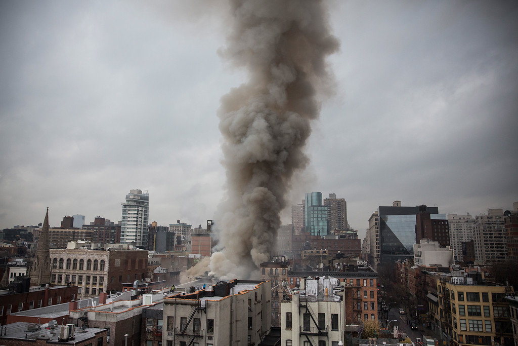 . NEW YORK, NY - MARCH 26:  Smoke rises from a burning building after an explosion on 2nd Avenue on March 26, 2015 in New York City.  The seven alarm fire drew firefighters from across the city. A number of injuries have been reported. (Photo by Andrew Burton/Getty Images)