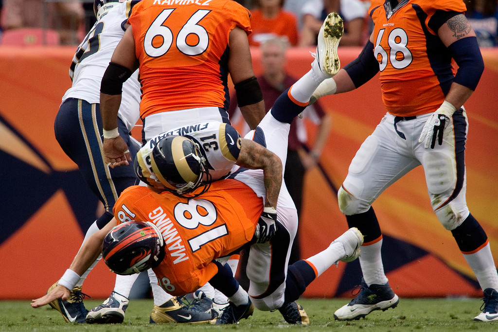 . DENVER, CO - AUGUST 24: Cortland Finnegan (31) of the St. Louis Rams puts a hit on Peyton Manning (18) of the Denver Broncos just after he threw a pass during the first half of action of an NFL preseason game at Sports Authority Field at Mile High on August 24, 2013. This is the third game of the preseason for the Broncos. (Photo by AAron Ontiveroz/The Denver Post)