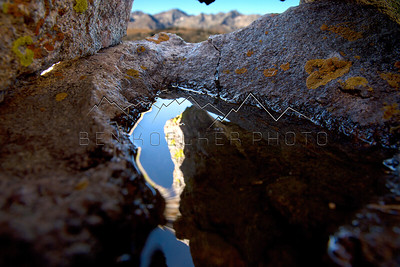 Golddust Mountain, CO and it's sawtooth ridge framed in rocks with reflection from a puddle