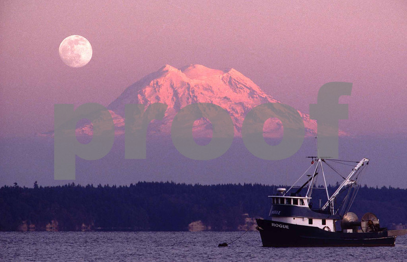 A full moon rises over Mt. Rainier with the Rogue fishing boat anchored in the Nisqually Reach of Puget Sound.