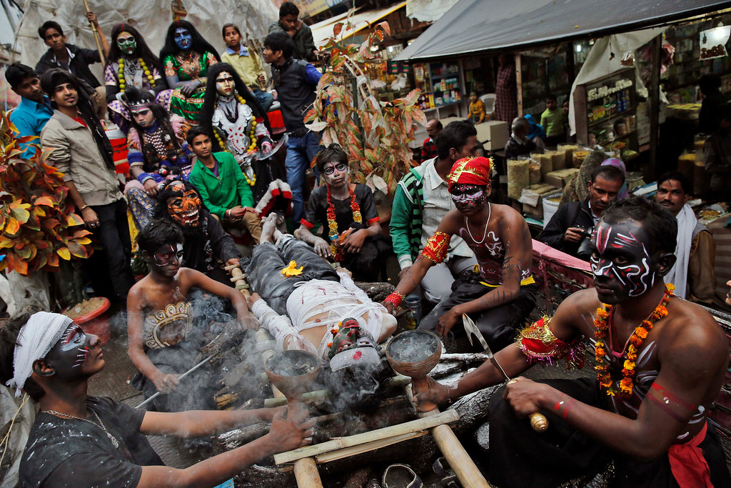 """. A Hindu devotee dressed as a demon lies on a ladder representing a funeral pyre during a \'Shivratri\' procession in Allahabad, India, Thursday, Feb. 27, 2014. \""""Shivaratri\"""", or the night of Shiva, is dedicated to the worship of Lord Shiva, the Hindu god of death and destruction. (AP Photo/Rajesh Kumar Singh)"""