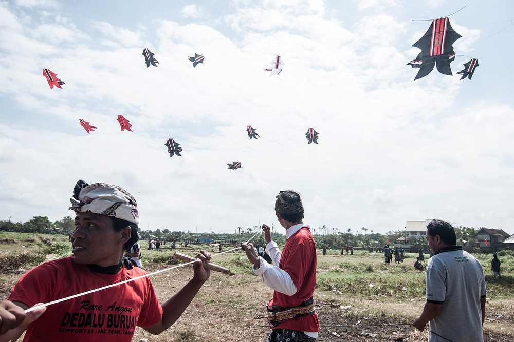 . Participants pull the string to fly the traditional kites during the Bali Kite Festival on July 26, 2013 in Denpasar, Bali, Indonesia. The event is a seasonal religious festival, which is intended to send a message to Hindu Gods to create abundant harvests and crops. Aproximately 1121 traditional kites are flown during the three day annual Festival.  (Photo by Putu Sayoga/Getty Images)