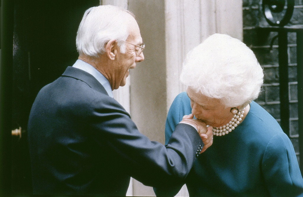 . America\'s first lady Barbara Bush kisses the hand of Denis Thatcher, husband of Britain\'s Prime Minister Margaret Thatcher, on arrival at No. 10 Downing Street, London, on June 1, 1989. (AP Photo/Dave Caulkin)