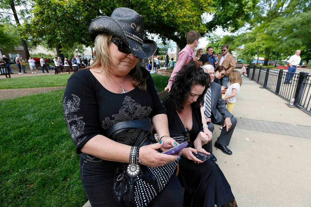 . Dawn McClintock (L) of Delaware updates her facebook status as she listens to the public memorial service for country music legend George Jones at the Grand Ole Opry House in Nashville, Tennessee, May 2, 2013.  REUTERS/Harrison McClary