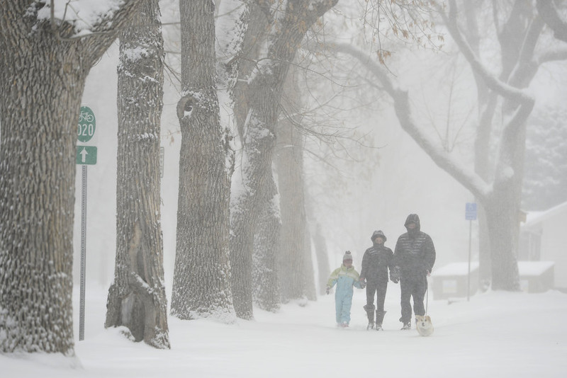 . Bob Goodyear walks Rosie (the corgi) as he walks with Suzanne Martin and her granddaughter, Zoe Martin, in front of University Park Elementary in south Denver. Snow is expected to fall throughout the day. (Photo by AAron Ontiveroz/The Denver Post)