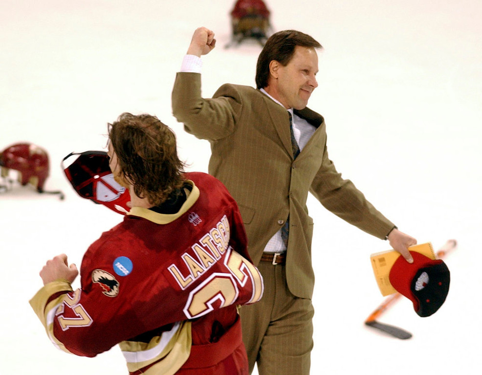 . Denver University head coach, George Gwozdecky, celebrates his teams victory over North Dakota at the NCAA West Regional Hockey championships at the World Arena in Colorado Springs on Saturday night. Du won 1-0. Matt Laatsch, #27, skates past the coach in celebration. THE DENVER POST/ ANDY CROSS