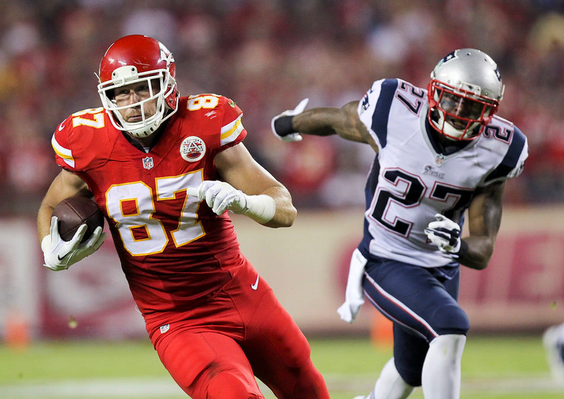 . Kansas City Chiefs tight end Travis Kelce, left, runs past New England Patriots strong safety Tavon Wilson after catching a pass for a 33-yard gain during the second quarter of an NFL football game Monday, Sept. 29, 2014, in Kansas City, Mo. (AP Photo/Ed Zurga)