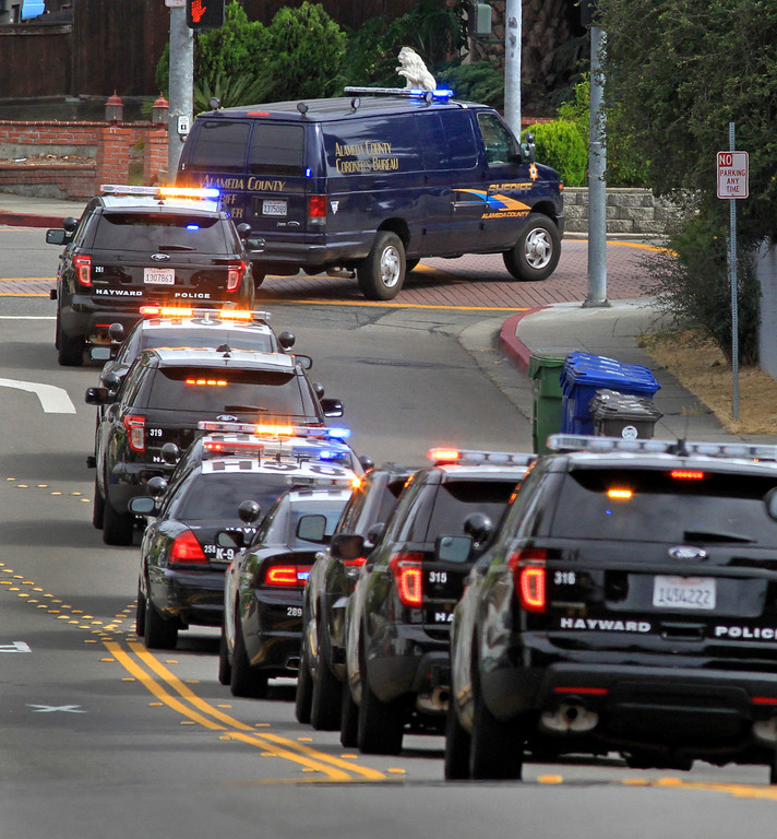 . Hayward police escort the Alameda County Coroner\'s van carrying their fellow officer, Sgt. Scott Lunger, as they leave Eden Medical Center in Castro Valley, Calif., on Wednesday, July 22, 2015.  Lunger was shot and killed in a shooting during a traffic stop early Wednesday morning. (Laura A. Oda/Bay Area News Group)