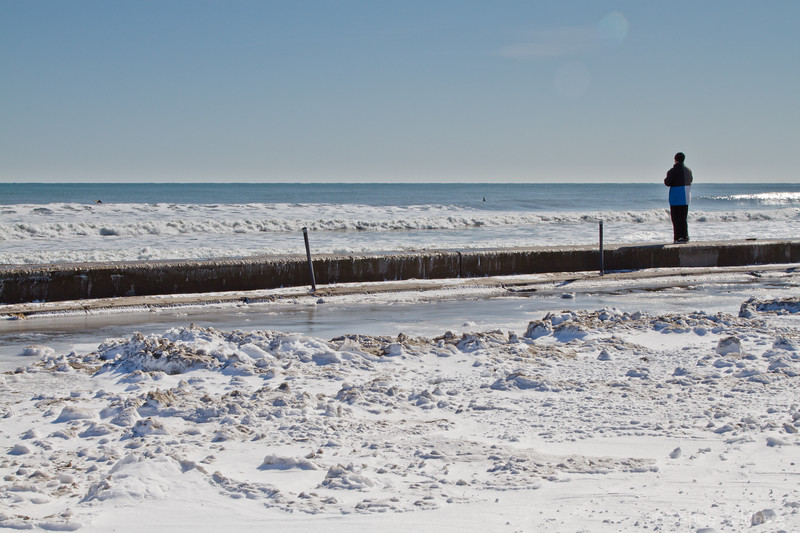 An ocean watcher, standing on the low wall separating the parking lot at Jenness State Beach Park from what is usually the beach. Today it was just the ocean, no beach.