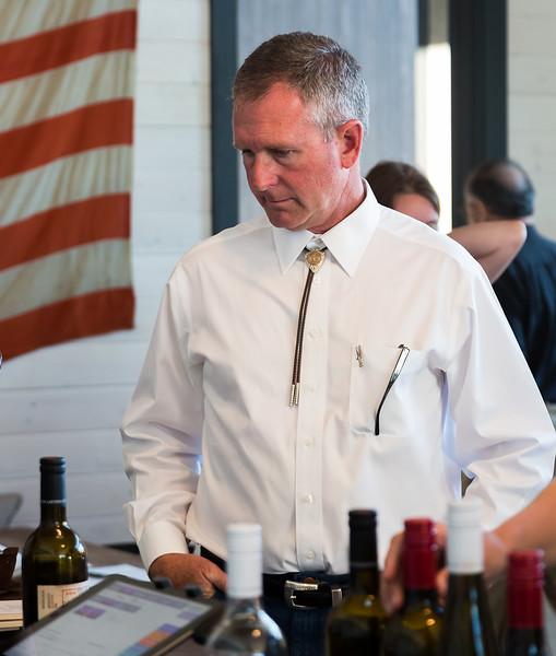 Wedding attendee looks over wine at wedding in Eastern WA.