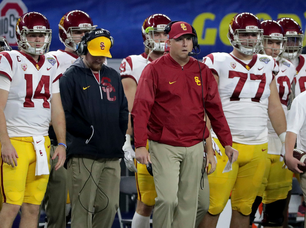 . Southern California coach Clay Helton, center, stands on the sidelines with quarterback Sam Darnold (14), guard Chris Brown (77) and others during the first half of the Cotton Bowl NCAA college football game against Ohio State in Arlington, Texas, Friday, Dec. 29, 2017. (AP Photo/LM Otero)