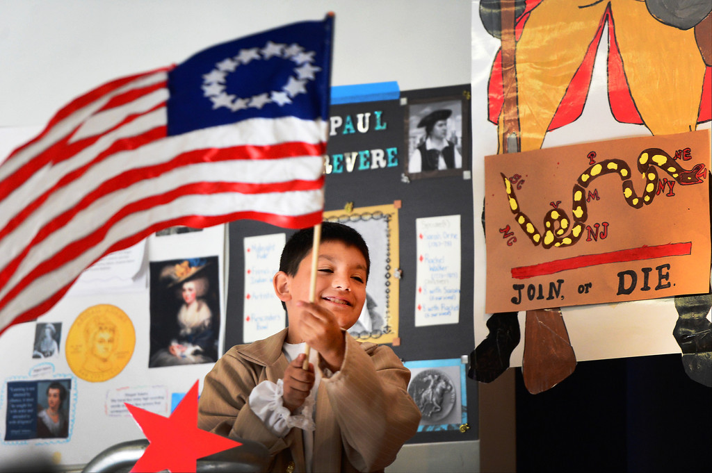 . Damien Aguirre, 10, waves, a Colonial  American Flag at Tracy Elementary School during a fifth-grade Colonial Festival Tuesday morning, March 26, 2013 at the Baldwin Park school. In one month the students completed a report, learned two songs and two dances. Grecia Herrera, the school\'s nutritional aid, made the dresses and boys\' suits. (SGVN/Staff Photo by Sarah Reingewirtz)