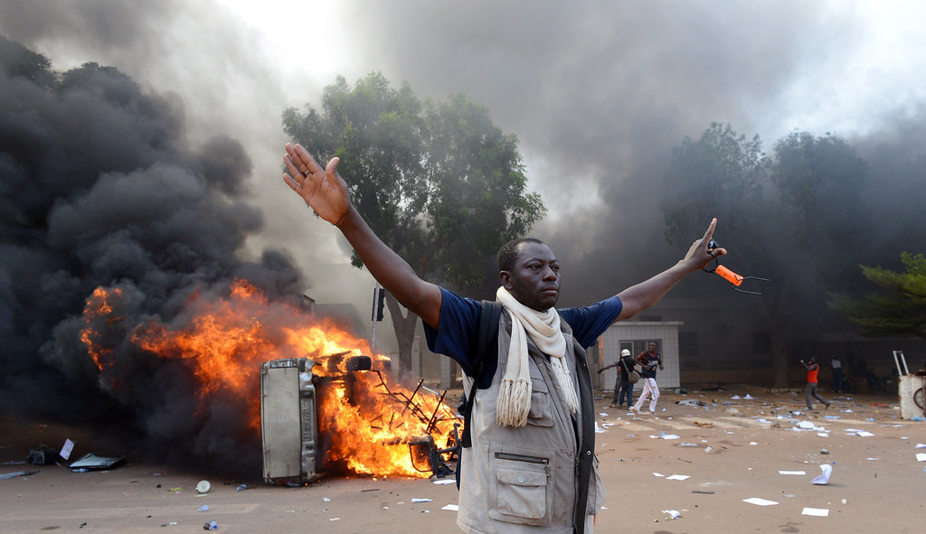 . A man stands in front of a burning car, near the Burkina Faso\'s Parliament where demonstrators set fire on cars parked, on October 30, 2014 in Ouagadougou, as they protest at plans to change the constitution to allow President Blaise Compaore to extend his 27-year rule.  SSOUF SANOGO/AFP/Getty Images