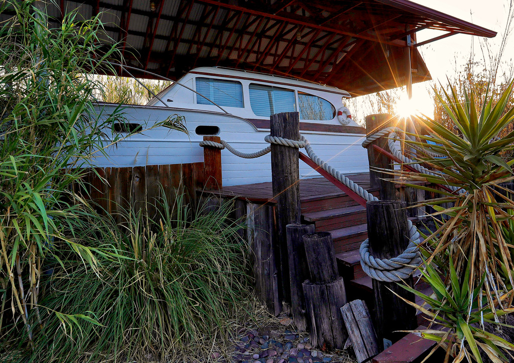 . The sun rises behind the stern of a 38-foot 1947 Chris Craft Yacht dry docked at the Shady Dell Trailer Court, Wednesday, April 26, 2017, in Bisbee, Ariz. The yacht offers a v-shaped berthing area and sleeps two. After lying dormant for years, the Shady Dell reopened in 1996 with the intention of reviving its 1950\'s atmosphere of an authentic trailer court and became a travel destination of it\'s own. (AP Photo/Matt York)