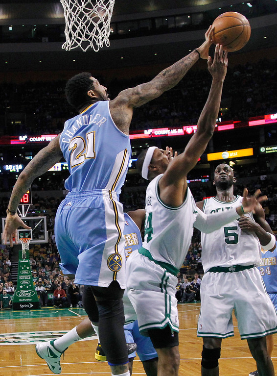 . Denver Nuggets guard Wilson Chandler (21) blocks a shot-attempt by Boston Celtics forward Paul Pierce (34) as forward Kevin Garnett (5) looks on during the first half of an NBA basketball game in Boston, Sunday, Feb. 10, 2013. (AP Photo/Elise Amendola)