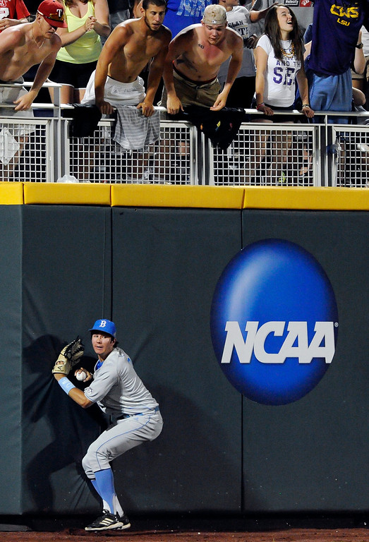 . UCLA outfielder Christoph Bono catches a fly ball hit by North Carolina State\'s Trea Turner to end the eighth inning of an NCAA College World Series baseball game in Omaha, Neb., Tuesday, June 18, 2013. (AP Photo/Eric Francis)