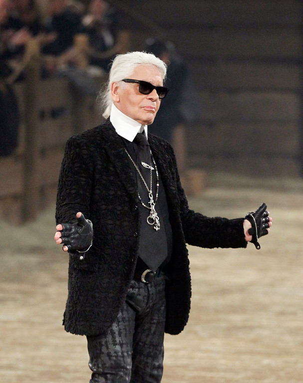 ". Chanel designer Karl Lagerfeld takes a bow at the end of his Metiers d\'Art fashion show, Tuesday, Dec. 10, 2013, in Dallas. For more than a decade, designer Lagerfeld has picked a city linked to the house for the theme of the show staged each December to highlight the work of its artisans. Fashion house founder Gabrielle ""Coco\"" Chanel visited Dallas in 1957 at the invitation of Stanley Marcus, who led Neiman Marcus, the Dallas-based luxury retailer founded by his family. (AP Photo/Tony Gutierrez)"