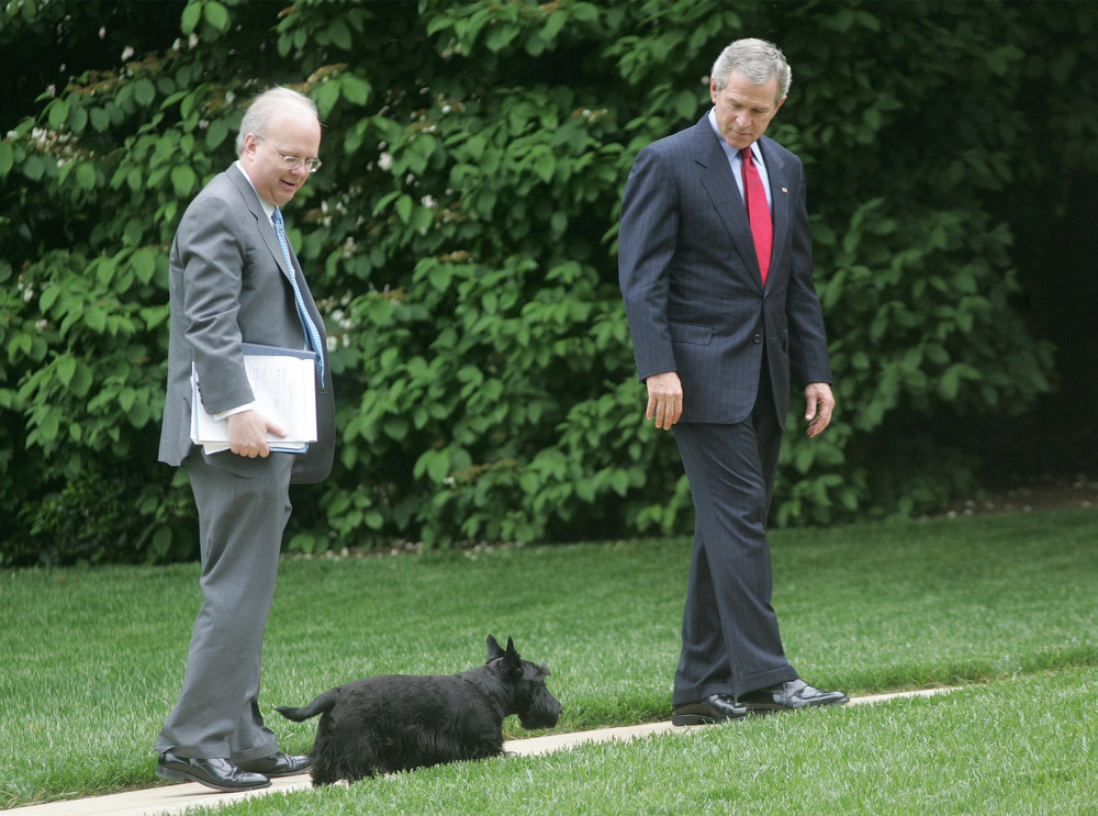 . President Bush and Karl Rove, deputy chief of staff, left, wait for Bush\'s dog Barney to catch up after returning to the White House. Bush was returning from speaking to a gathering of the National Association of Realtors at the Marriott Wardman Park Hotel in Washington, Friday, May 13, 2005. The audience welcomed his message on private accounts for Social Security and tax breaks for entrepreneurs and homeowners. (AP Photo/Ron Edmonds)