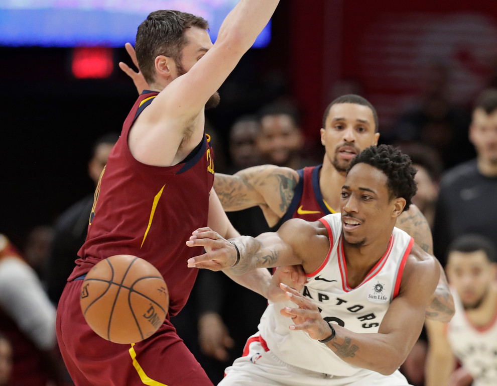 . Toronto Raptors\' DeMar DeRozan (10) passes around Cleveland Cavaliers\' Kevin Love (0) in the second half of an NBA basketball game, Wednesday, March 21, 2018, in Cleveland. (AP Photo/Tony Dejak)