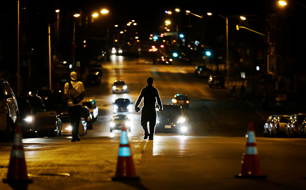 . Youths walk down the street away from police in riot gear after a 10 p.m. curfew went into effect Thursday, April 30, 2015, in Baltimore. The curfew was imposed after unrest in the city over the death of Freddie Gray while in police custody. (AP Photo/David Goldman)