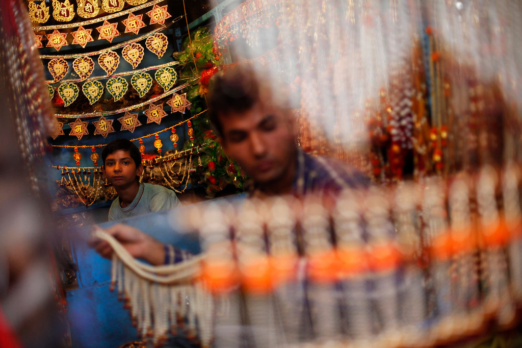 . An Indian shopkeeper, selling decorative items, is assisted by a young boy as they wait for customers on the eve of Diwali, the Hindu festival of lights, in New Delhi, India, Saturday, Nov. 2, 2013. Hindus light up their homes and pray to Lakshmi, the goddess of wealth, during the festival which will be celebrated on Nov. 3. (AP Photo/Altaf Qadri)