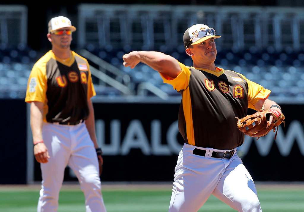 . U.S. Team\'s Carson Kelly, of the St. Louis Cardinals, fields a ball as Hunter Dozier, of the Kansas City Royals, looks on, prior to the All-Star Futures baseball game against the World team, Sunday, July 10, 2016, in San Diego. (AP Photo/Lenny Ignelzi)