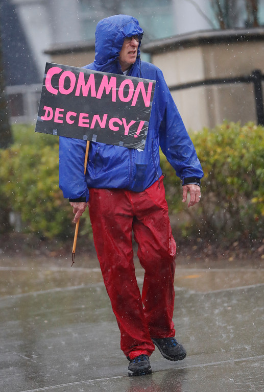 . A man makes his way through a heavy downpour to a protest march Saturday, Jan. 21, 2017, in Atlanta. Thousands of people marched through Atlanta one day after President Donald Trump\'s inauguration. (AP Photo/John Bazemore)