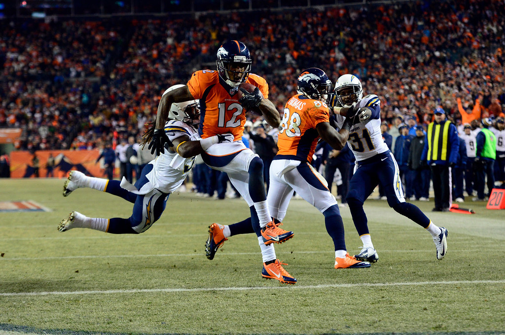 . Denver Broncos wide receiver Andre Caldwell (12) jumps into the end zone scoring a touchdown for the Broncos in the second half.  This touchdown brought the score to Chargers 24 and Broncos 17.  The Denver Broncos vs. the San Diego Chargers at Sports Authority Field at Mile High in Denver on December 12, 2013. (Photo by AAron Ontiveroz/The Denver Post)