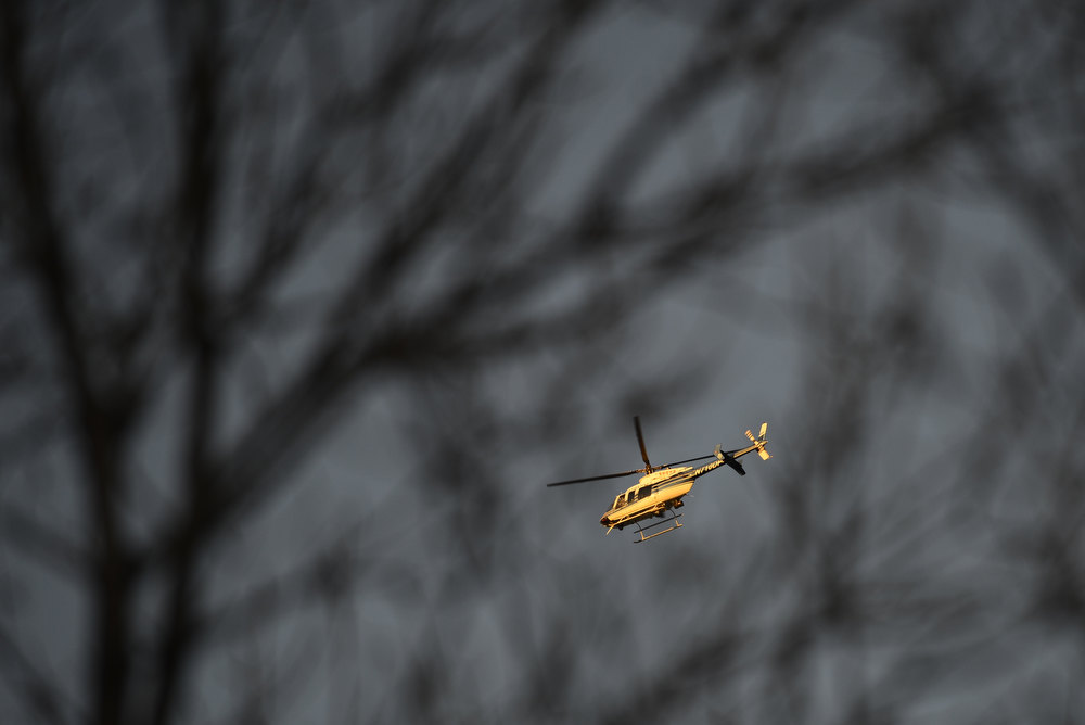 . A helicopter flies over the scene where police secure the area near 39th and Osage where a police officer was injured during what witnesses described as a red Dodge truck wrecking into a tree and a man exiting the truck who began shooting and fled on foot on Wednesday, January, 16, 2013. AAron Ontiveroz/The Denver Post