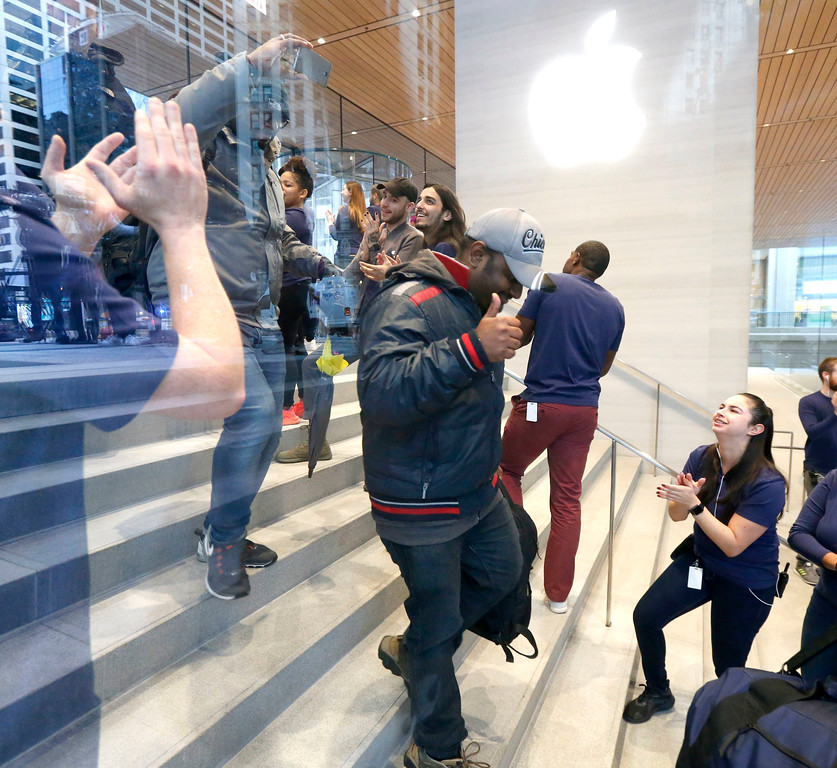 . Consumers receive applause from Apple employee as they arrive to buy the Apple iPhone X at the new Apple Michigan Avenue store along the Chicago River Friday, Nov. 3, 2017, in Chicago. (AP Photo/Charles Rex Arbogast)