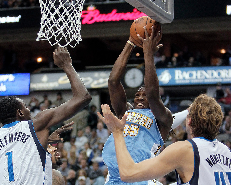 . Denver Nuggets forward Kenneth Faried (35) attempts a shot as Dallas Mavericks\' Samuel Dalembert (1) and Dirk Nowitzki (41) defend during the first half of an NBA basketball game Monday, Nov. 25, 2013, in Dallas. (AP Photo/Brandon Wade)