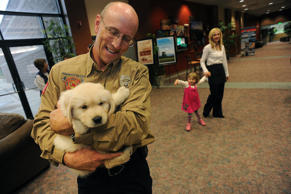 . LONGMONT, CO - OCTOBER 29:   Ted Plank, left, holds 5 week old Chinook at Life Bridge Community Church in Longmont, Co on October 29, 2013. (at right is Melissa Garcia.)  Chinook was born just a few days after the flood.  Her mother was taken out of the Pinewood Springs area via a Chinook helicopter to escape the floods.  Because of this dramatic effort to get the dog to the vet before she gave birth Geri and her husband named this puppy Chinook.  (Photo By Helen H. Richardson/ The Denver Post)