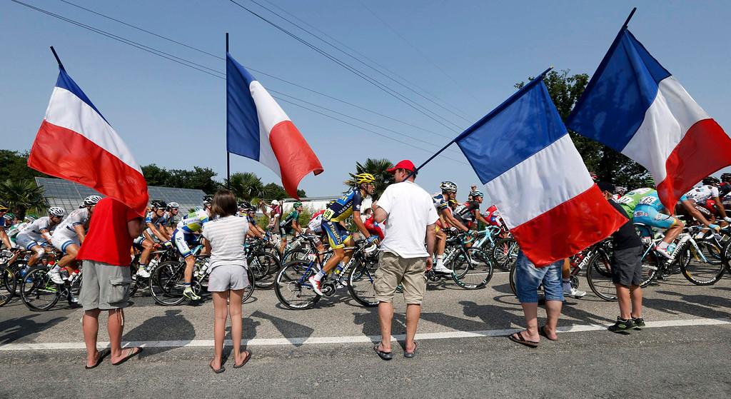 . The pack of riders cycles past supporters waving French flags during the 191 km fourteenth stage of the centenary Tour de France cycling race from Saint-Pourcain-Sur-Sioule to Lyon, July 13, 2013.       REUTERS/Jean-Paul Pelissier