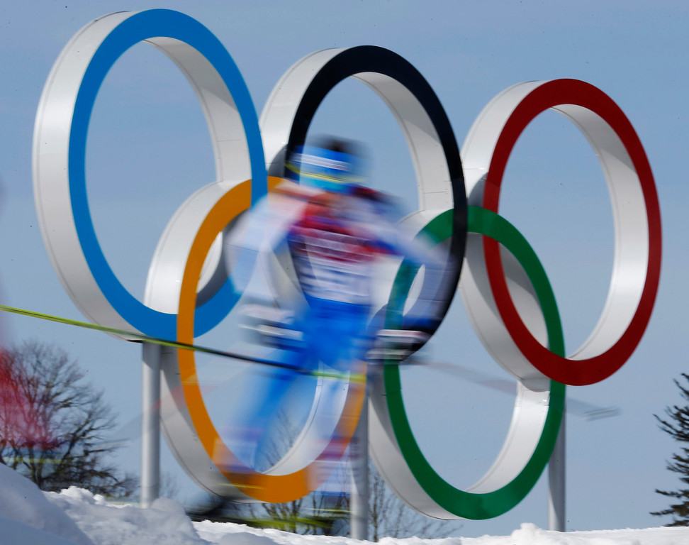 . In this photo taken with slow shutter speed athletes pass by the Olympic rings during the men\'s 50K cross-country race at the 2014 Winter Olympics, Sunday, Feb. 23, 2014, in Krasnaya Polyana, Russia. (AP Photo/Dmitry Lovetsky)