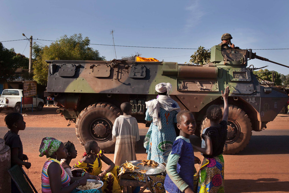 Description of . Villagers wave to French military as they pass the the town of Konobougou, Mali January 17, 2013. European Union states will send more than 200 military personnel to train Mali government forces in the fight against Islamist rebels. Western stakes in the crisis were underlined when Islamist gunmen took dozens of foreign and local workers hostage at an Algerian desert gas facility on Wednesday, demanding that France pull its troops out of Mali. REUTERS/Joe Penney