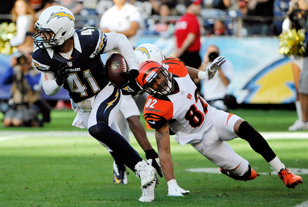 Description of . San Diego Chargers defensive back Corey Lynch (41) runs upfield after grabbing an interception as Cincinnati Bengals wide receiver Marvin Jones, right, watches during the second half of an NFL football game, Sunday, Dec. 2, 2012, in San Diego. (AP Photo/Denis Poroy)