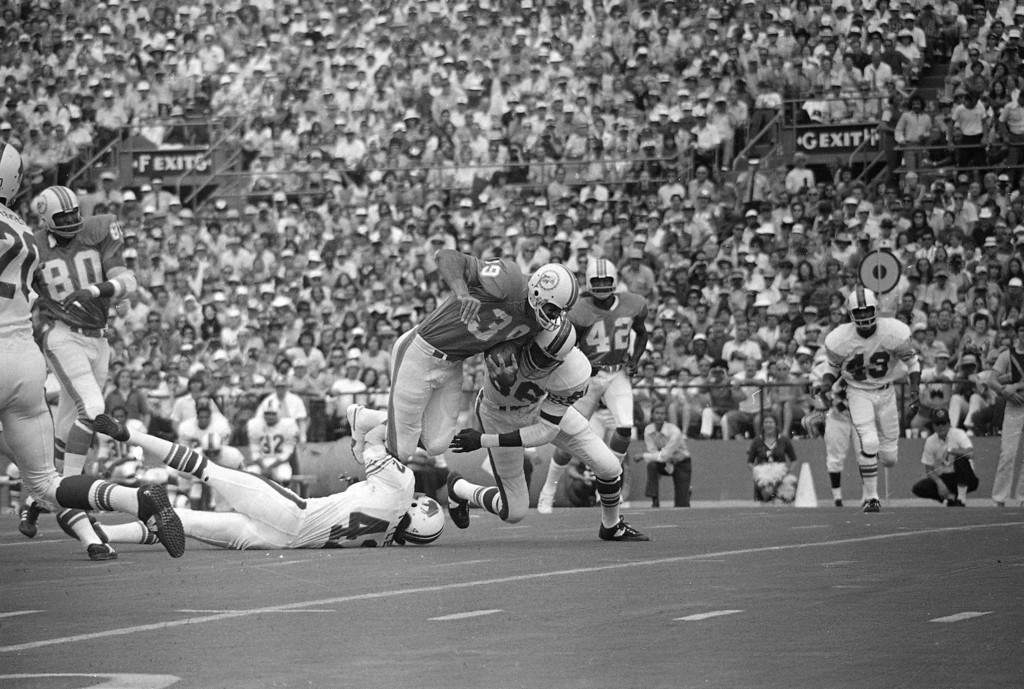 . Miami Dolphins fullback Larry Csonka (39) grinds out the yardage in their game against the Buffalo Bills at The Orange Bowl in Miami, Fla., Oct. 22, 1972. Making the stop in the first quarter are Bills\' Maurice Tyler (42) and Dave Washington (86). (AP Photo)