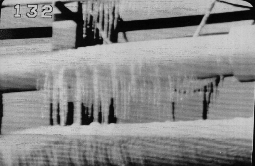 Description of . An ice buildup on the launch structure around the Space Shuttle caused another delay in the launch on Jan. 28, 1986. Water was allowed to run, as a safety precaution, on the launch tower because of freezing temperature in the area the previous night. It was feared ice could fall onto the shuttle during launch causing damage to the spacecraft. Denver Post Library Archive