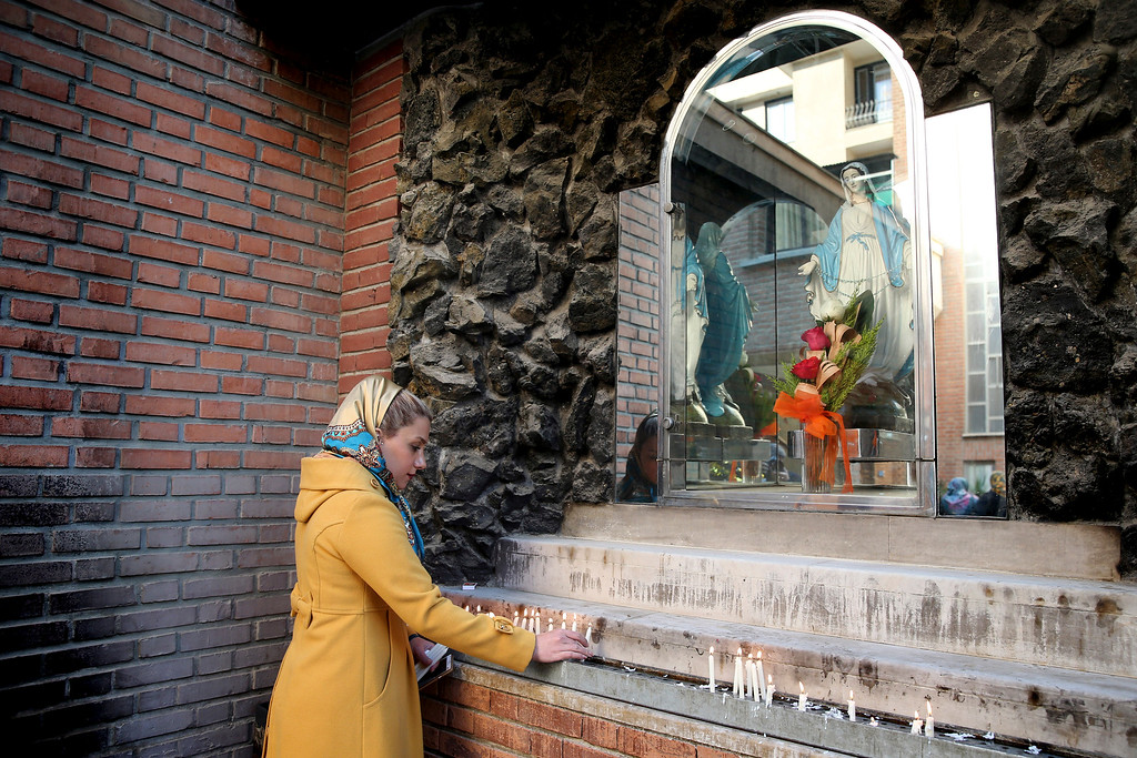 . An Iranian Christian woman lights candle in Christmas Day at the Saint Mary Chaldean-Assyrian Catholic church in Tehran, Iran, Thursday, Dec. 25, 2014. Iran\'s minority group of Christians are celebrating Christmas and preparing for the new year. According to official figures, around 120,000 Christians live in Iran, mostly in central and northwestern parts of the country. Iranian Christians represent part of the parliament and freely practice their religion as allowed under the constitution. Other minorities, such as the Jews and Zoroastrians, are recognized in the same way by the law. (AP Photo/Ebrahim Noroozi)