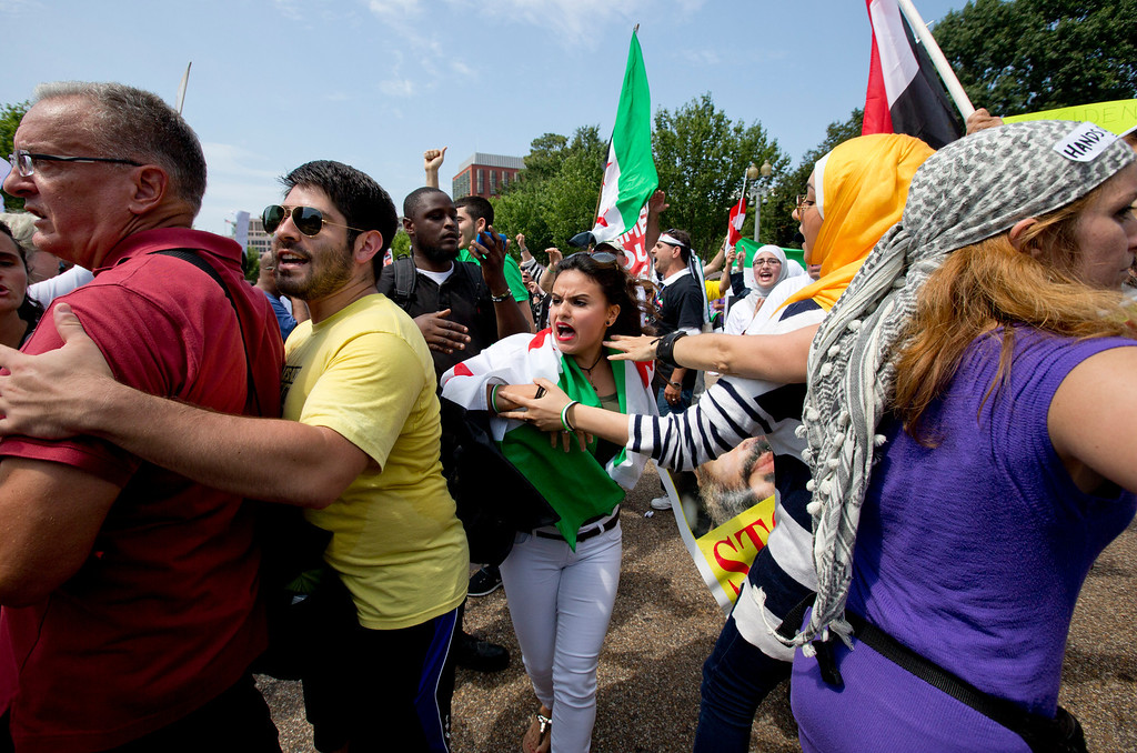 """. Pushing and shoving erupts among Syrian protesters, some for and some against U.S. military action in Syria, as they demonstrate in front of the White House in Washington Saturday, Aug. 31, 2013. The woman in the middle with a Syrian flag draped over his shoulders identified herself as Asmaa Al-Ghafari, a \""""Syrian American revolutionist.\"""" (AP Photo/Carolyn Kaster)"""