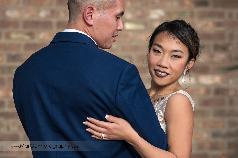 bride looking forward and holding hand at groom's back at Sunol's Casa Bella