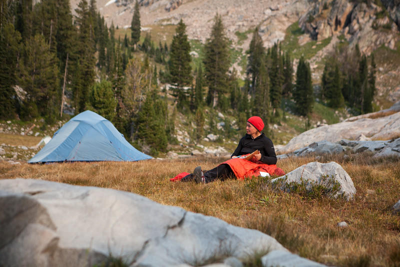 A researcher takes notes at camp during a chilly summer evening in the high Tetons