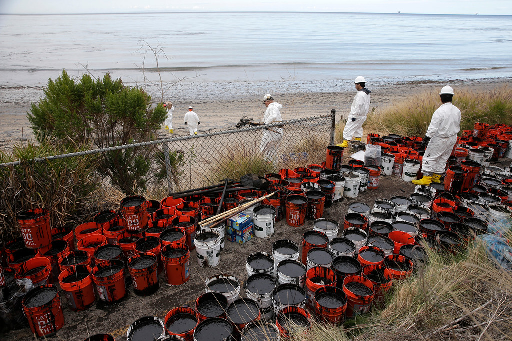 . Plastic buckets with oil collected from the beach are placed at the side at Refugio State Beach, north of Goleta, Calif., Thursday, May 21, 2015. More than 7,700 gallons of oil has been raked, skimmed and vacuumed from a spill that stretched across 9 miles of California coast, just a fraction of the sticky, stinking goo that escaped from a broken pipeline, officials said. (AP Photo/Jae C. Hong)
