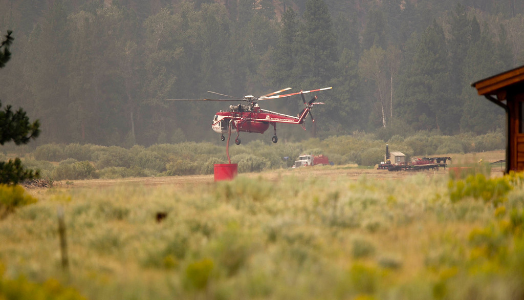 . A type one sky crane helicopter sucks fire retardant from a large barrel  near Dog Mountain in Pine, Idaho while fighting the Elk fire Wednesday Aug. 14, 29013.  (AP Photo/Idaho Statesman, Kyle Green)