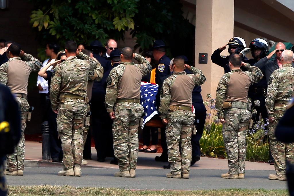 . Police officers from several law enforcement agencies and firefighters salute to the body of Hayward police Sgt. Scott Lunger as he is brought in a coffin during the procession from the Coroner\'s Bureau in Oakland to Chapel of the Chimes Memorial Park in Hayward, Calif., on Thursday, July 23, 2015. Lunger was killed during a traffic stop in early Wednesday. (Ray Chavez/Bay Area News Group)