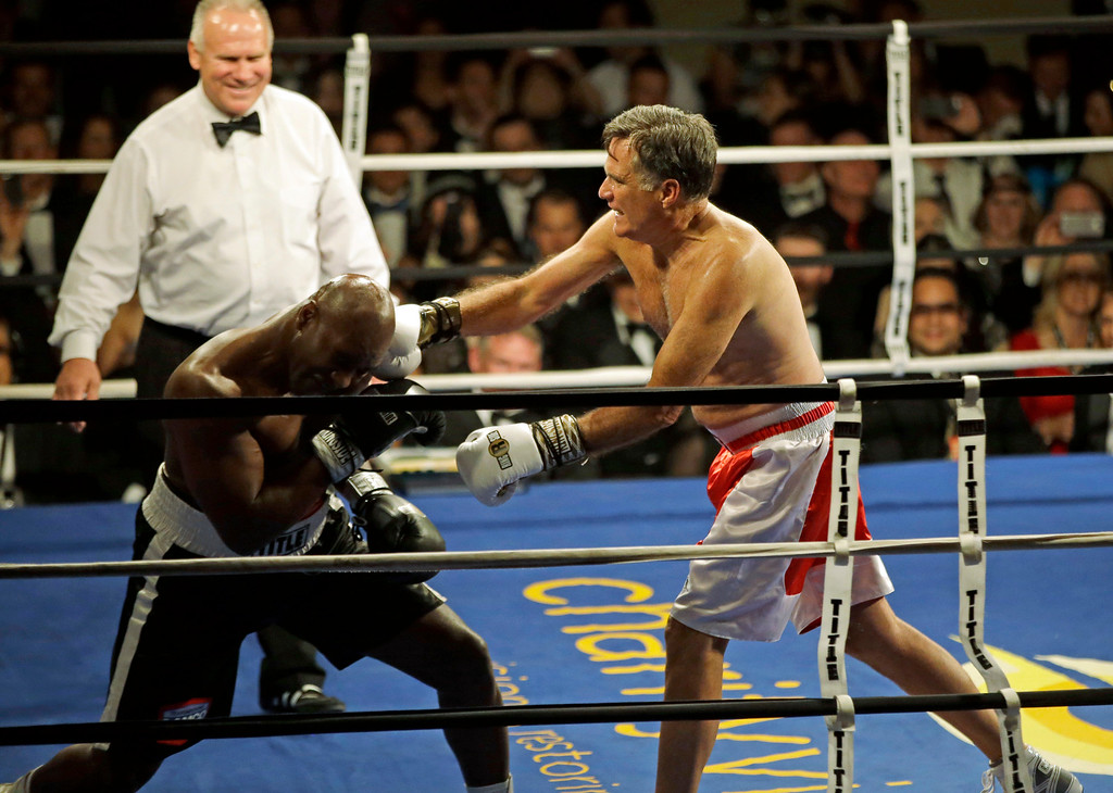 . Former Republican presidential candidate Mitt Romney, right, lands a punch against five-time heavyweight boxing champion Evander Holyfield while sparring during a charity fight night event Friday, May 15, 2015, in Salt Lake City. The black-tie event raised money for the Utah-based organization CharityVision, which helps doctors in developing countries perform surgeries to restore vision in people with curable blindness. (AP Photo/Rick Bowmer)