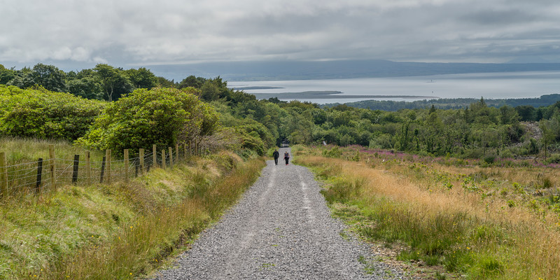 People walking on dirt road passing through field, Grange, County Sligo, Ireland