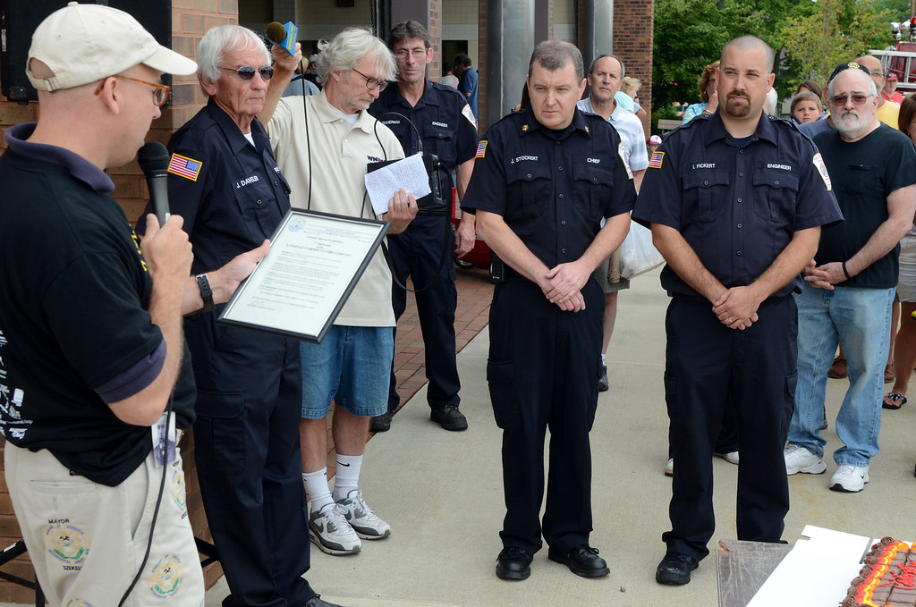 . Lansdale Mayor Andy Szekely ,L, presents a proclamation to Fairmount Fire Company Chief Joe Stockert (center) President Ian Fickert (R) and Fire Marshall Jay Davelar (2nd from L) during the Lansdale Founders Day  celebration and on Saturday August 23,2014. Photo by Mark C Psoras/The Reporter
